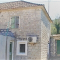 The stone house is for sale on a green, quiet street in the village of Zelenika.